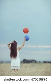 Dream, happiness - young girl in a field with flying balloons