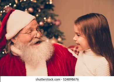 dream is real in christmastime! happy little cute girl sitting on the lap of aged Santa Claus and hugs at home near christmas tree
