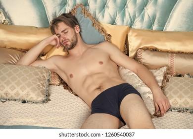 Dream, slumber concept. Man sleep in blue bed. Macho with sexy body in briefs in bedroom. Fashion, male underwear.