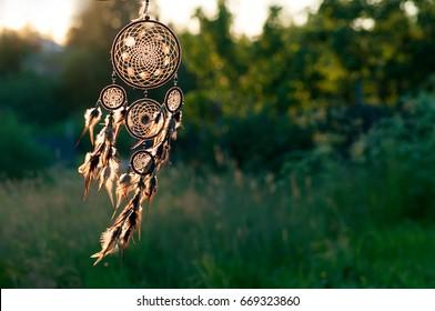 Dreamcatcher, american native amulet on sunset. Shaman