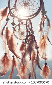 Dreamcatcher is flying in the sky,american boho indian symbol,beautiful feathers.