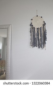 Dreamcatcher hung next to silver mirror.