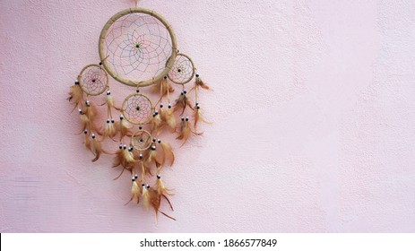 Dreamcatcher on a pink background. Place for text. Selective focus. Handmade dreamcatcher with thread feathers and hanging rope beads.