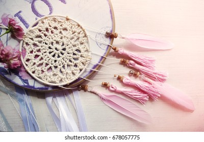 Dreamcatcher with pink feathers on a wooden background. Ethnic design, boho style, tribal symbol.