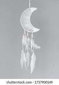 Dreamcatcher in the shape of a Crescent moon on a gray background. Interior decoration. Native American Dreamcatcher.