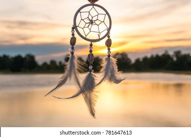 Dreamcatcher at sunset time in windy day with orange of sky and water reflections in background.