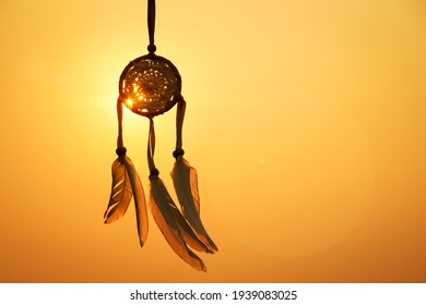 Dreamcatcher with white feather thread and beaded string. Handmade Dreamcatcher.The light of the setting sun.