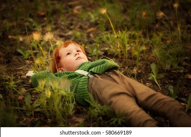 Dreamer. Cute red-haired boy is laying on the grass and looking at the sky. Image with selective focus and toning.