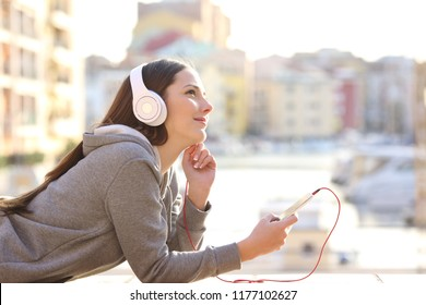Dreamer girl listening to music with headphones and a smart phone on vacation