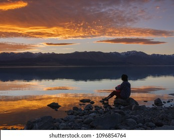 dreamer, silhouette of woman sitting along the lake at sunset, human strength, psychology concept
