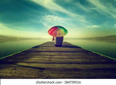 Dreamer,The man with the umbrella in colors is sitting on a fishing pier