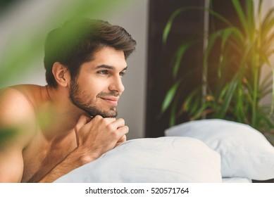 Dreamful guy relaxing in bedroom