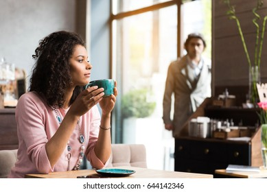 Dreamful woman is drinking coffee in cafeteria. She is sitting at table and looking forward pensively. Man is coming into door on background
