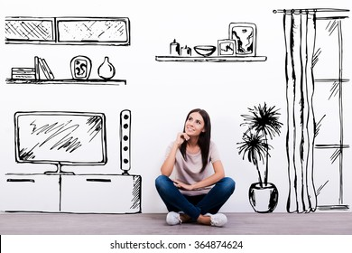 Dreaming about new apartment. Cheerful young woman smiling while sitting on the floor against white background with drawn home interior