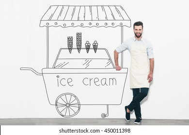Dreaming about new business. Handsome young man in apron standing in front of the wall and leaning at the pencil drawn ice cream cart
