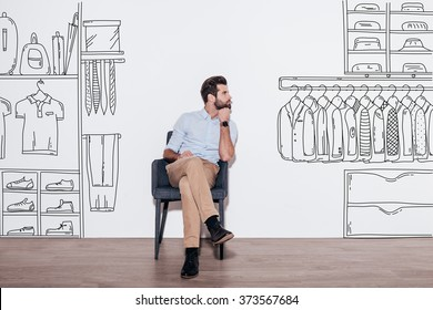 Dreaming about new wardrobe. Young handsome man keeping hand on chin and looking away while sitting in the chair against illustration of closet in the background
