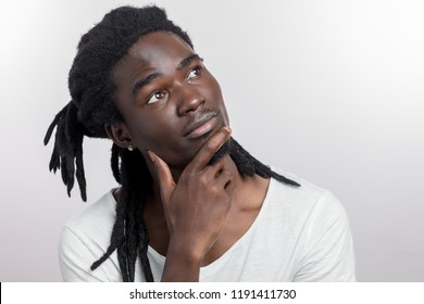 Dreaming African Man With Dreadlocks On White Background With Hands On Chin Or Chest