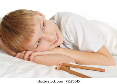 dreaming boy on white floor with a pen