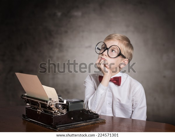 Dreaming boy with the typewriter. Retro style portrait