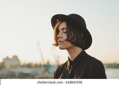 Dreaming closed eyes young lovely girl portrait wih black stylish hat. Big city lifestyle mood.  Urban port background.
