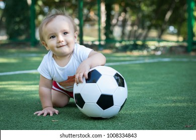 Dreaming little boy at the stadium with a soccer ball. Future football star