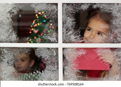 Dreaming little girl holding red envelope to Santa and looking for him through the frosty window, her little brother and blurred lights of Christmas Tree on background, winter holiday concept