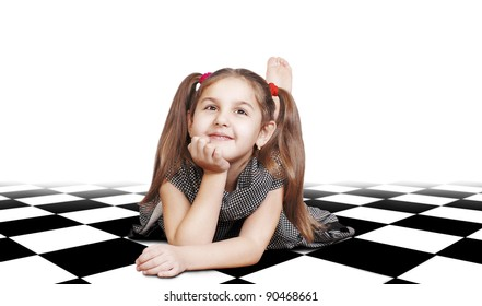 Dreaming  little girl with long hair lying on checkered surface