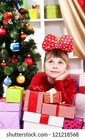 Dreaming little girl in red dress surrounded by gifts in festively decorated room