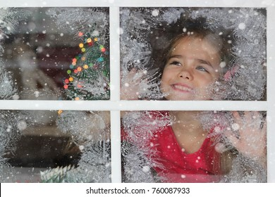 Dreaming little girl in red t-shirt waiting for Santa and looking on the first snow with rapture, view through the frosty window, blurred lights of Christmas Tree on background, winter holiday concept