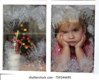 Dreaming little toddler boy in red t-shirt waiting for Santa near frosty window, view through the window, ill boy, blurred lights of Christmas Tree on background, winter holiday concept, portrait