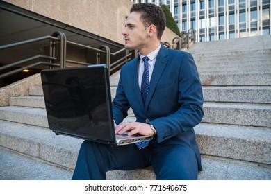Dreaming man in elegant suit posing on stairs with laptop on knees looking away.