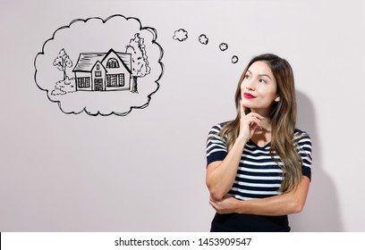 Dreaming of new home with young businesswoman in a thoughtful face