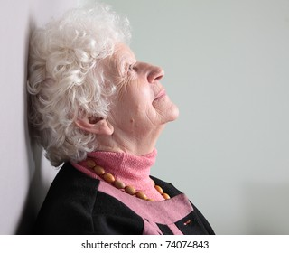 Dreaming old woman. isolated against grey background