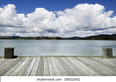 Dreaming on a empty wooden pier looking at island landscape with big white clouds on blue sky. No People. copy space