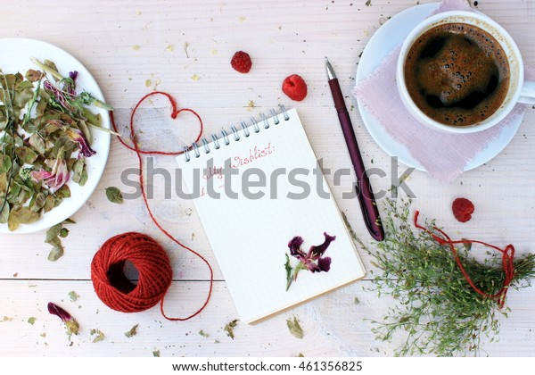 Dreaming theme: notebook with handwritten text and cup of morning coffee, bunch of grass and heart. Romantic decor