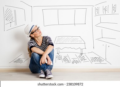 Dreaming woman in headset over drawn living room background. Young pretty female thinking of furnishing her new apartment.