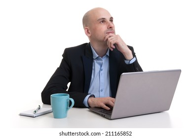 dreaming young business man looking up while working at laptop computer