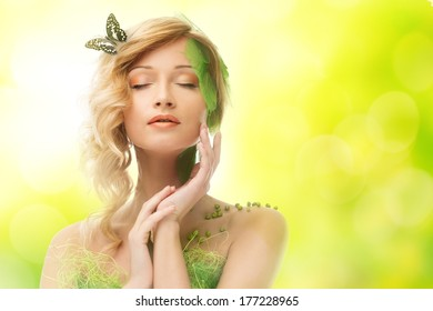 Dreaming young woman in conceptual spring costume with butterfly in her hair