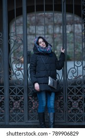 Dreaming young woman, with her eyes closed, posing on the background of a vintage wrought-iron gate in the courtyard of an old building. Winter day in the city.