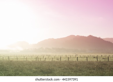 Dreamlike early morning scene of a farm and mountains with a pink and green neon filter applied. Ferndale, Humboldt County, California, USA.
