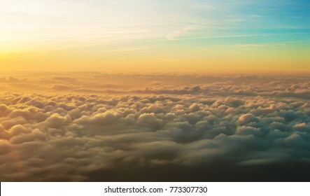 Dreamlike view of many white fluffy clouds at sunrise in warm yellow light. Blue sky on the horizon. Air travel on a sunny cloudless day. Feeling of wander and splendor