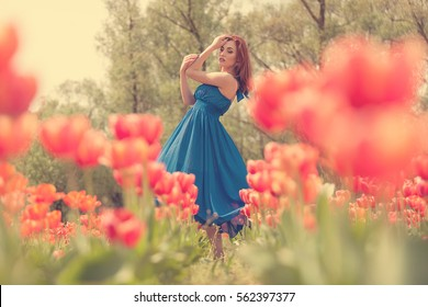Dreammy woman portrait in flower field. Sprins and summer. Romance and happiness. Young beautiful woman in tulip field