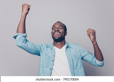 Dreams come true! Portrait of excited cheerful handsome delightful joyous wearing casual denim shirt guy raising his hands up, isolated on grey background