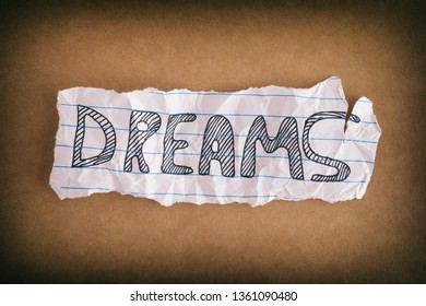 Dreams. Crumpled piece of paper with the word Dreams on brown paper background. Close up.