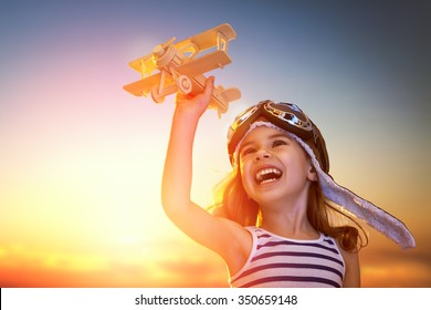 dreams of flight! child playing with toy airplane against the sky at sunset