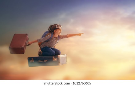 Dreams of travel! Child flying on a suitcase against the backdrop of sunset.