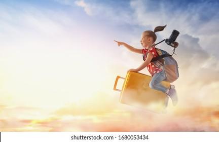 Träume von Reisen! Kind, das auf einem Koffer auf dem Hintergrund des Sonnenuntergangs fliegt.