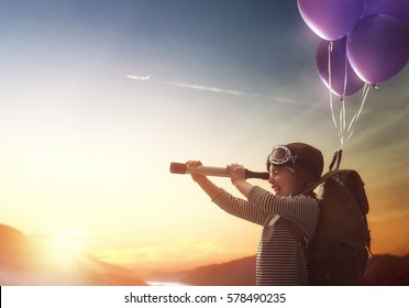 Dreams of travel! Child flying on balloons against the backdrop of a sunset. - Shutterstock ID 578490235