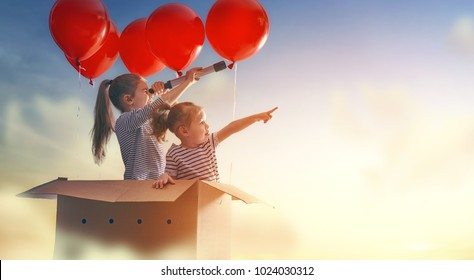 Dreams of travel! Two children are flying in cardboard box with air balloons.