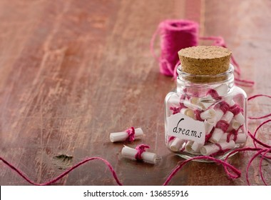 Dreams written on a white rolled paper in a glass jar on rustic vintage wooden background with copy space, dreaming optimism concept